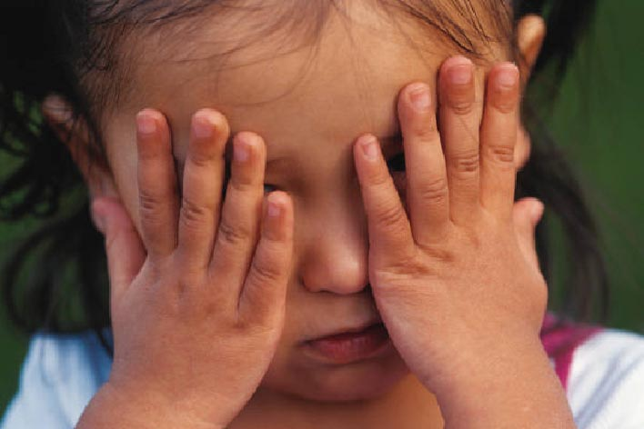 Young child with hands over her eyes