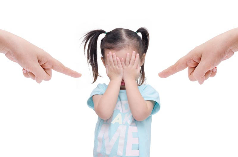 Fingers pointing at young girl with hands over face
