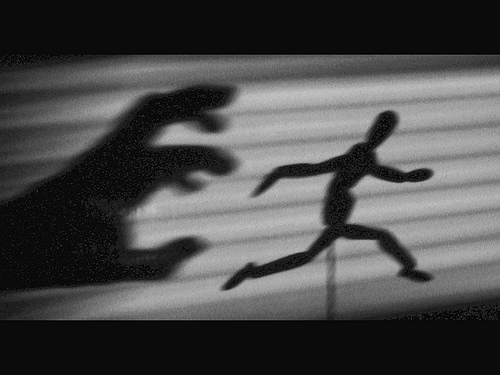 shadow puppet running from grasping hand shadow
