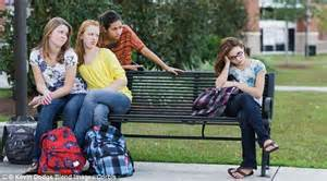 Group of teen girls on park bench excluding one girl